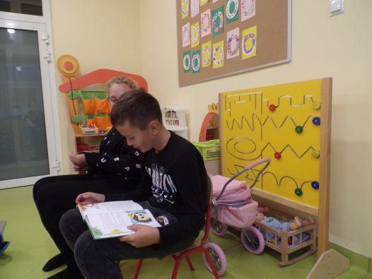 Uczniowie czytają bajki przedszkolakom